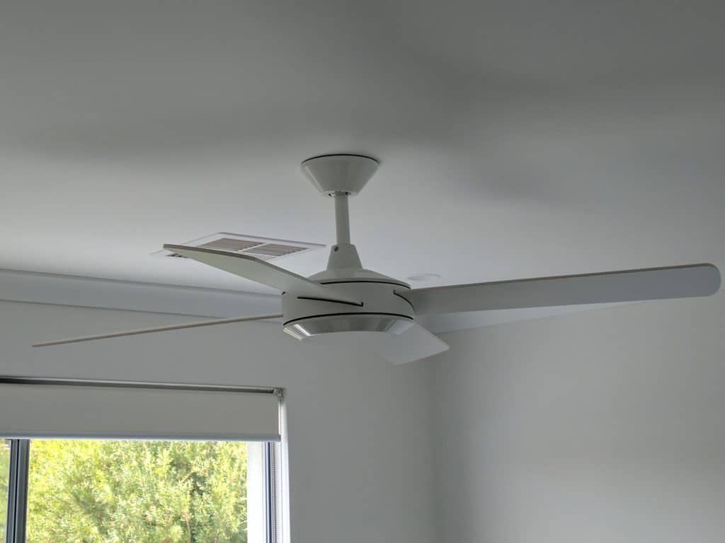 white ceiling fan in bedroom with downlights